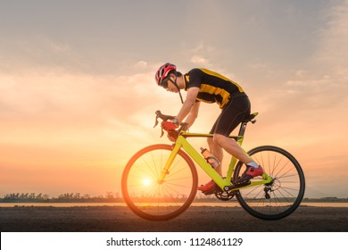 Road bike cyclist man cycling. Biking sports fitness athlete riding bike on an open road to the sunset.