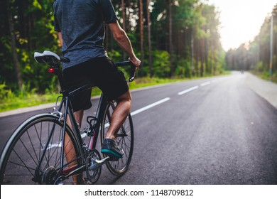 Road bike cyclist, man cycling on empty road in sunset