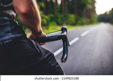 Road bike cyclist, man cycling on empty road in sunset close up view on hand holding handlebar