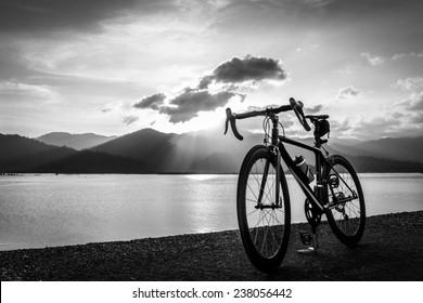 road bike on waterfront black and white photo, sunset nature b/w