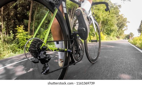 Road bike, original point of view. Pedal, chain and wheels of bicycle