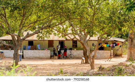 ROAD TO BISSAU, GUINEA B. - MAY 1, 2017: Unidentified local boys stand near the house in a village in Guinea Bissau. Still many people in the country live in poverty