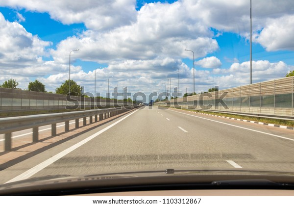 road, blue sky background with clouds, view from the car.