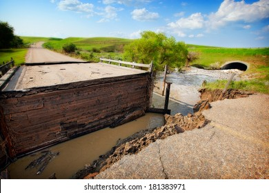 A road and bridge damaged by muddy, flood waters.