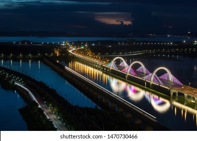 road bridge and railway on the lake at night