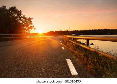 Road and bridge with white border signs during a sunset, asphalth reflecting colors from the sun. Sunny evening in Grisslehamn, Sweden