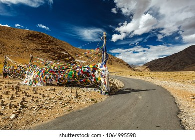 Road and Buddhist prayer flags (lungta) at Namshang La pass in Himalayas. Ladakh, India