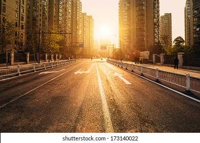 road and buildings at city with sunset