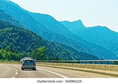 Road and car and Alpine mountains on the background. Austria in summer.