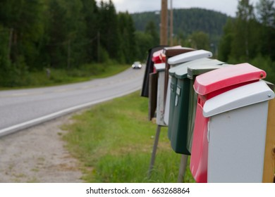 Road, car and colorful mailboxes in summer cloudy day.
