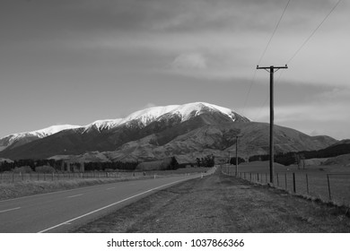 Road from Christchurch to Arthur Pass, New Zealand, South Island. Black&White image, depicting the highway with powerlines and the snow covered mountains in th background.