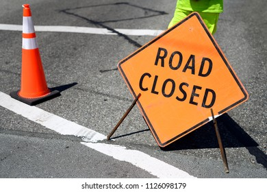 Road closed ahead traffic sign on the road with a body part of construction flagger