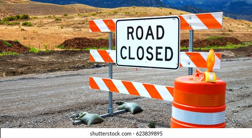 Road closed sign with cone on dirt road (close up panorama)