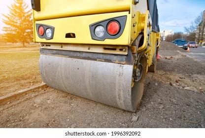 Road compaction works, road roller close up. Light tandem roller for soil compaction and asphalt patching. Road roller compact soil, preparation for asphalt paving.