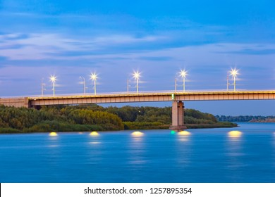 Road concrete bridge on supports across the Volga River, lampposts illuminate at dusk at night, green forest on the shore. New Bridge, Astrakhan, Russia.