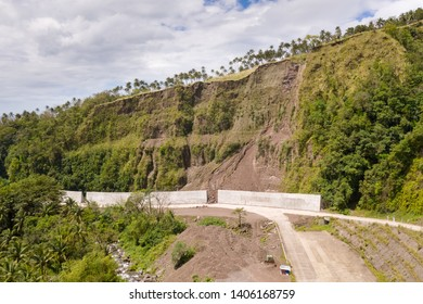Road with concrete fences on Camiguin Island, Philippines. Protection of the road from rockfalls and landslides. The collapse of the soil on the road in the highlands.