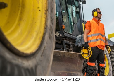 Road Construction Business. Caucasian Heavy Machinery Operator in His 30s with Noise Reduction Headphones and Hat Protection Helmet in a Hand.