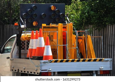 Road construction companies vehicle. The ute loaded with traffic control signage and orange safety cones. Also directional portable traffic lights have been mounted to the back of the vehicle.