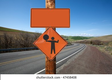 Road construction and flagger sign screwed on wooden pole against winding road