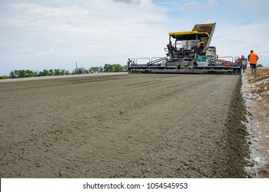 Road construction. Laying of concrete with heavy machines