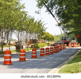 A road construction project with orange and white barrels