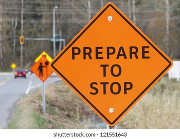 A road construction sign warns oncoming traffic and motorists/Prepare to Stop Sign/A construction sign warns motorists to prepare to stop.