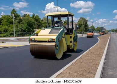 Road construction site. Asphalt roller compactor on site, compacting new asphalt pavement in urban modern city