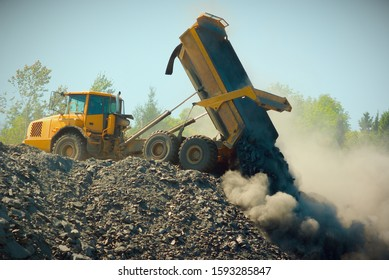 road construction site large yellow truck dumping rock