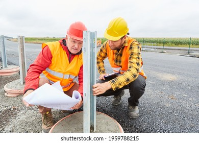 Road construction workers inspect construction for guardrails at the construction site