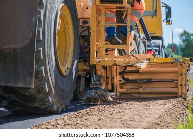 Road construction workers repairing highway road on sunny summer day. Loaders and trucks on newly made asphalt. Heavy machinery working on street. Road curbs being constructed with gravel
