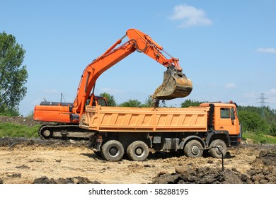Road construction works. Heavy machinery - excavator and dump truck.