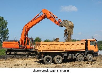 Road construction works in Poland. Heavy machinery - excavator and dump truck.