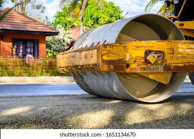 Road construction works with steamroller machine and asphalt finisher