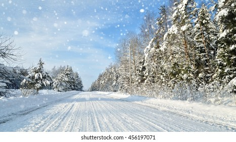 Road in a countryside in sunny winter day with snow falling. Classic snow covered winter landscape in Latvia
