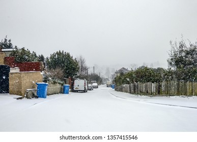 Road covered in snow with wheelie bins in suburbia