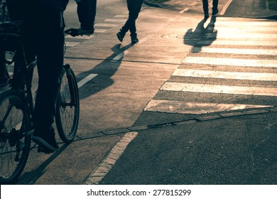 Road crossing with pedestrians feet and cyclist in city.