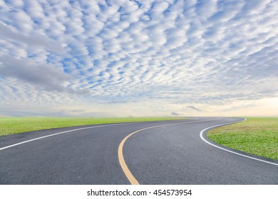 road curve with green grass and blue sky white cloud background