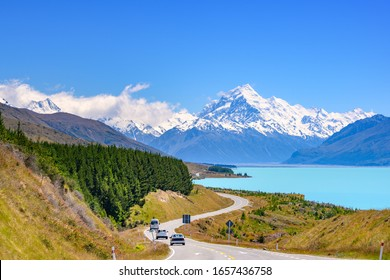 The road curves along Lake Pukaki and Mount Cook on a clear day at Peter's Lookout in the South Island of New Zealand.