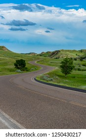 Road Curves Into The Distance through Theodore Roosevelt National Park
