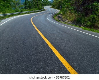 The road curves up the mountain. Line yellow and white road.
