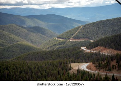 A road cuts through the thick forest high up in the mountains, a scenic byway for travelers heading over the summit