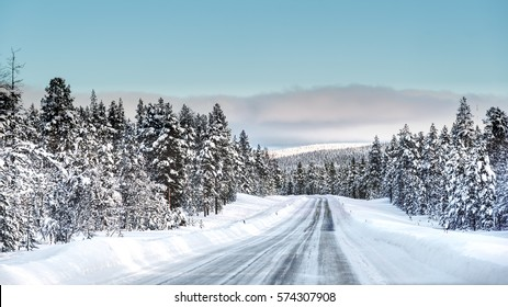 A road cutting through a forest covered with snow in a cold winter day with a layer of clouds over a horizon