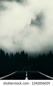 road in dark landscape with mountain shrouded in fog