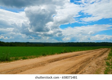 the road disappears in the distance among fields and forests