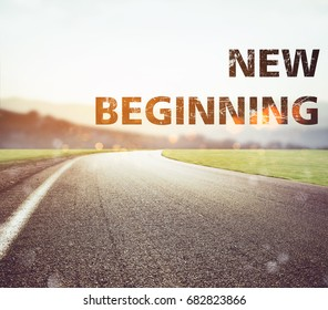 Road disappears from the view at sunset. Text new beginning