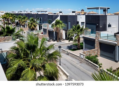 Road divides similar in a row modern exclusive spanish luxury villas two story residential houses new apartments in Torrevieja tourist resort city, Province of Alicante, Costa Blanca, Spain