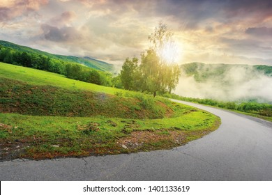road down the hill at sunrise. sun light come through the tree. cloudy sky above the distant mountain ridge. mysterious foggy weather.