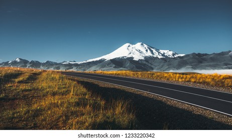 Road to the Elbrus mountain at sunrise, North Caucasus, Russia. The concept of a road trip