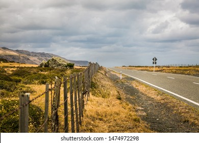 Road and fence converging at horizon, cape palliser coastline, n