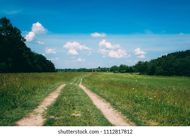 road, field, forest and cloudy sky in summer time